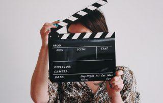 Frau hält eine Filmklappe vor ihr Gesicht